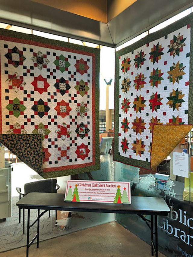 Quilts for silent auction hanging in library foyer